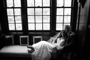 bride and groom in window sill; black and white