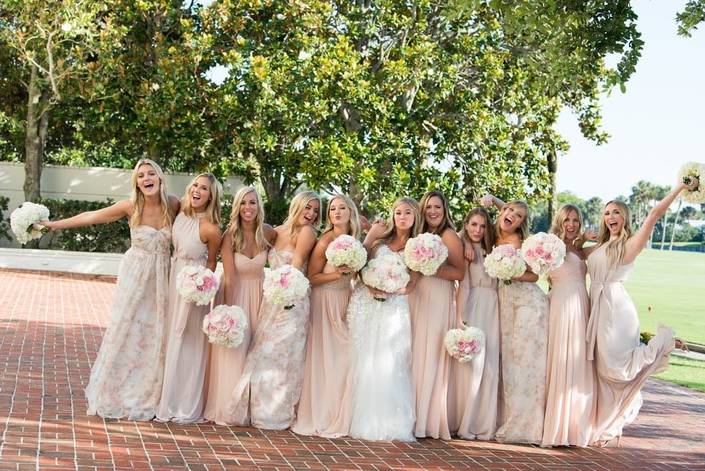 real bride Fallon on her wedding day in Florida and her bridesmaids in pale blush pink gowns.