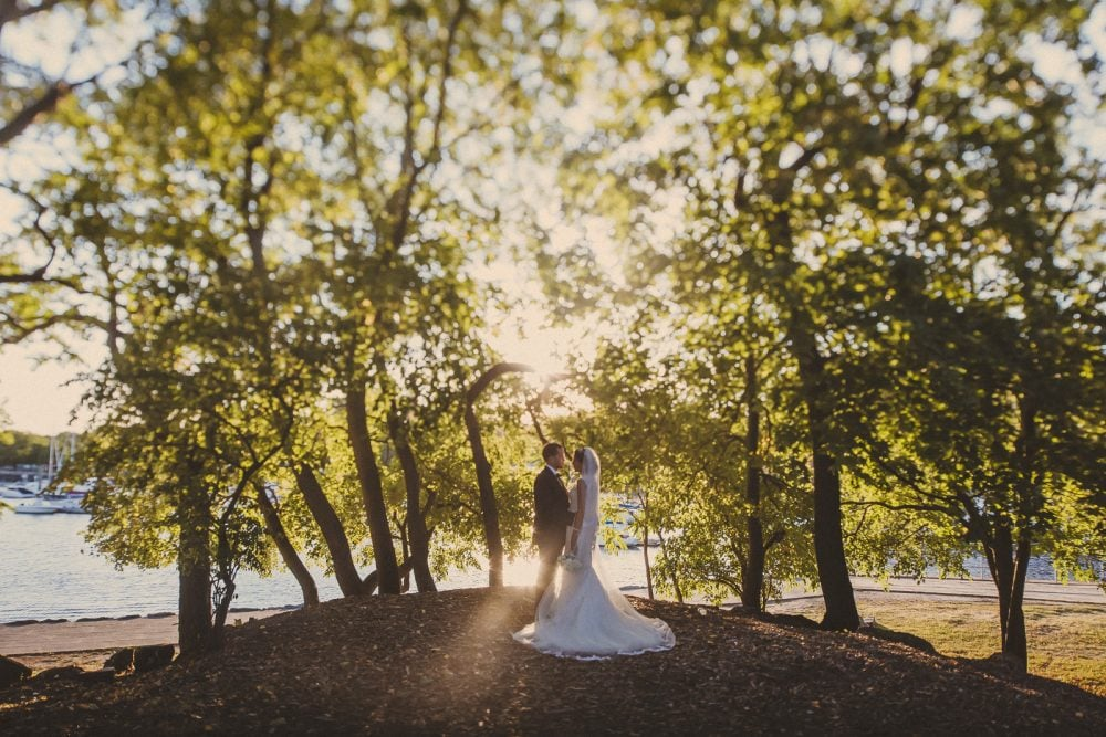 gorgeous bride with groom in a sunlit forest clearing on their wedding day