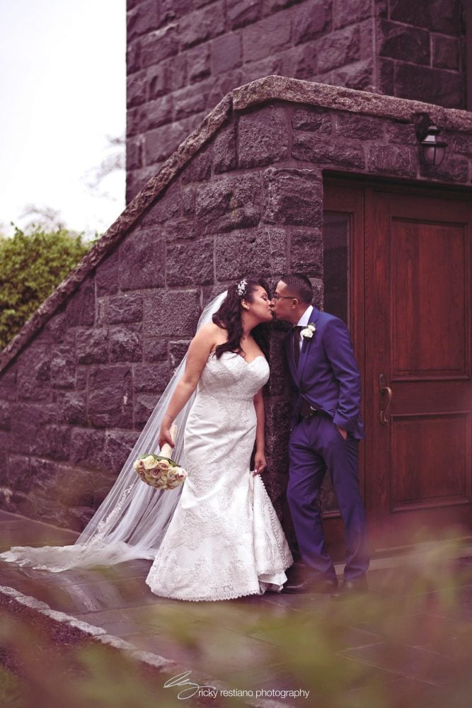 Real Bride Carolina and her groom sharing a kiss at the scenic wedding venue in New York.