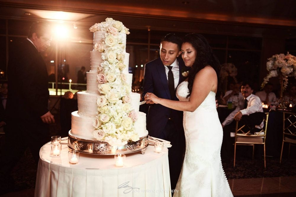 Real Bride Carolina cutting the wedding cake with the groom on their wedding day.