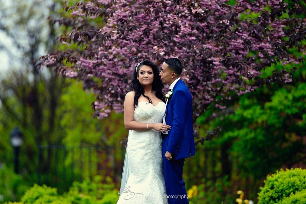 Bride Carolina and her groom in an orchard on their wedding day.