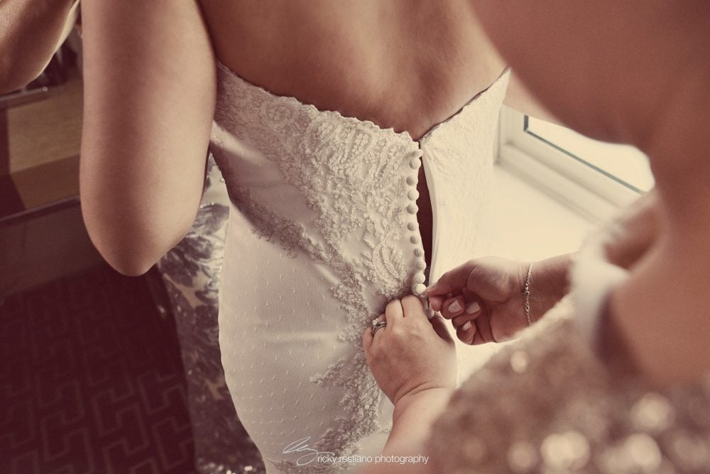 Carolina getting help with having her wedding gown clasped on her wedding day.