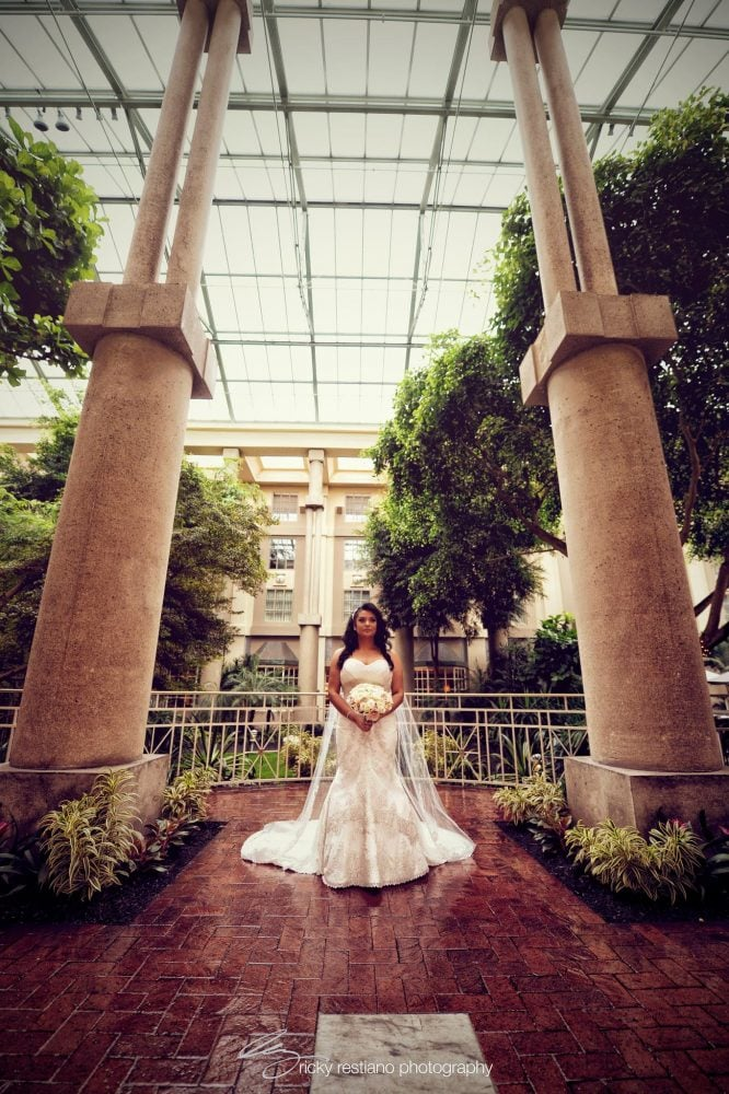 Stunning shot of Real Bride Carolina on her wedding day, framed by pillars, and dressed in her wedding gown by Matthew Christopher.