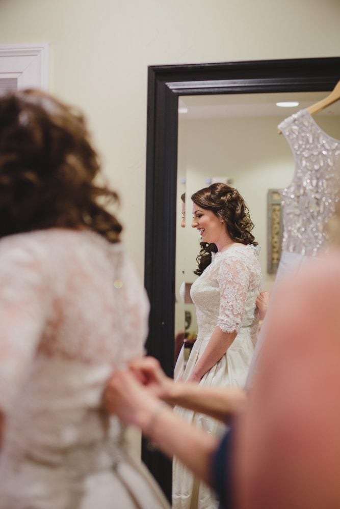 Bride getting help to put on her Paloma Blanca wedding gown.