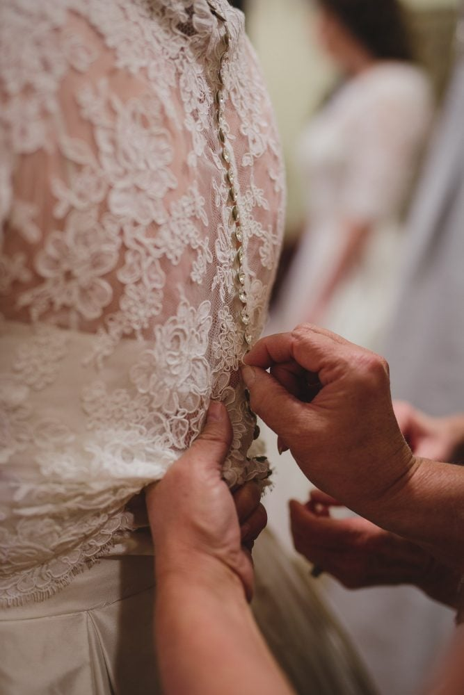 close-up of wedding gown being clasped.