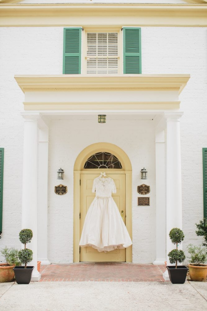 Wedding gown hanging in white door frame.