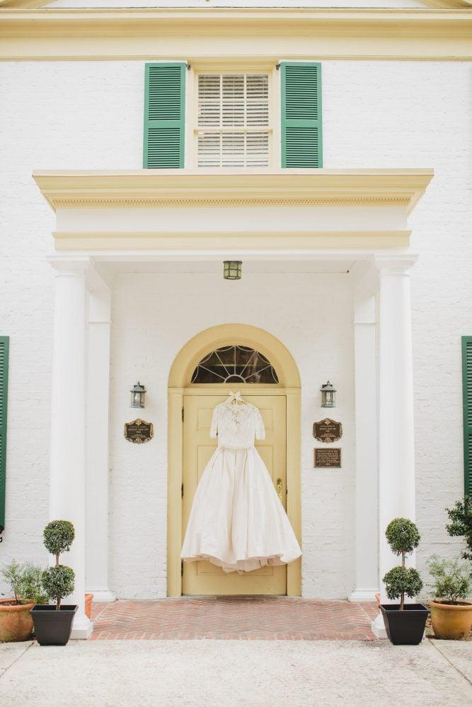 Wedding gown hanging in white door frame.