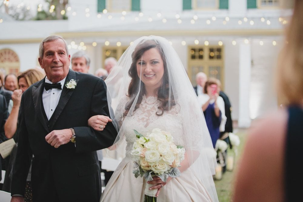 Real Bride Laura walking down the aisle with her father on her wedding day in veil and Paloma Blanca gown.
