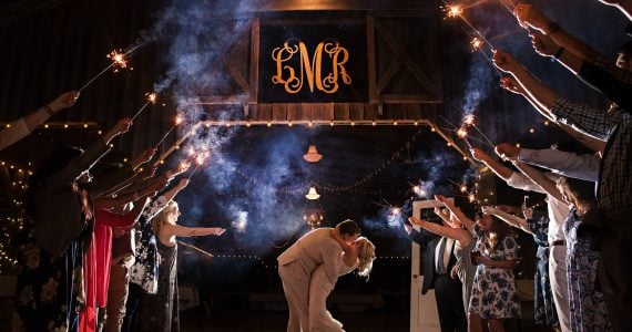 Real bride Lindsay and her groom sharing a dramatic kiss surrounded by sparklers and applause inside their barn venue.