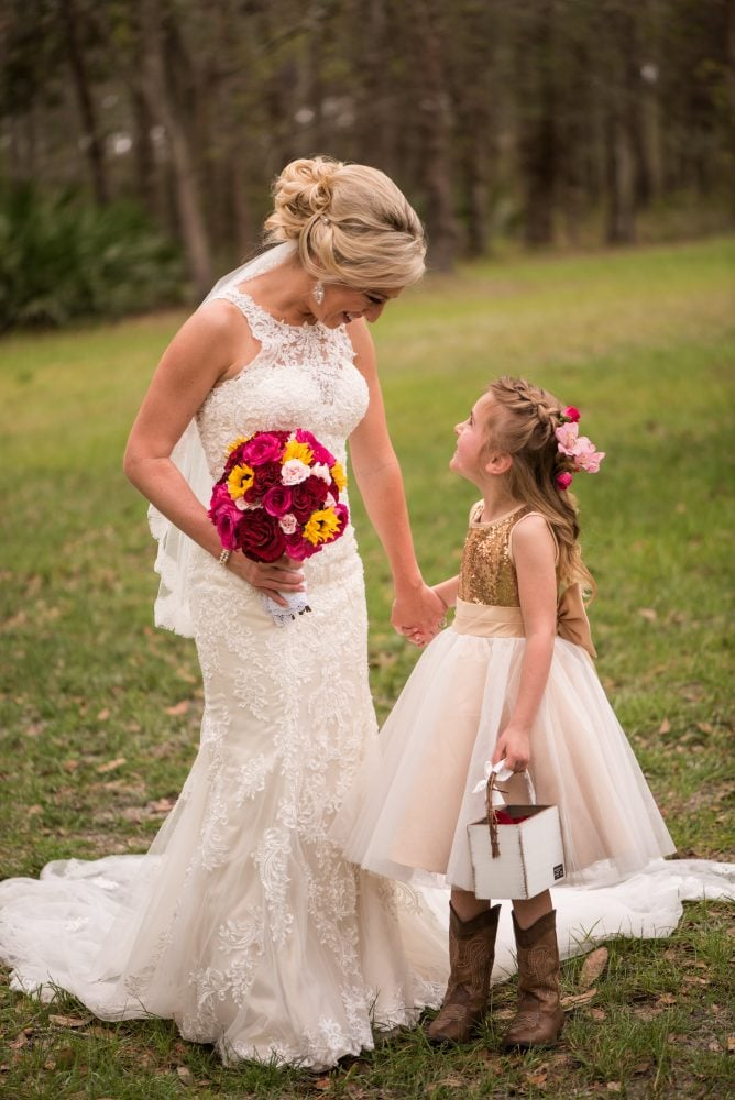 Bride on wedding day wearing wedding gown with flower girl and bridal bouquet.