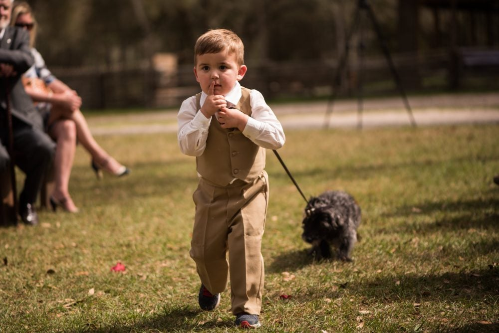 Adorable kid dragging a dark, scruffy dog by the leash in a field.
