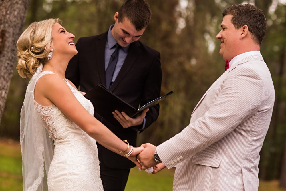 Bride and groom on wedding day with officiant, holding hands and smiling.