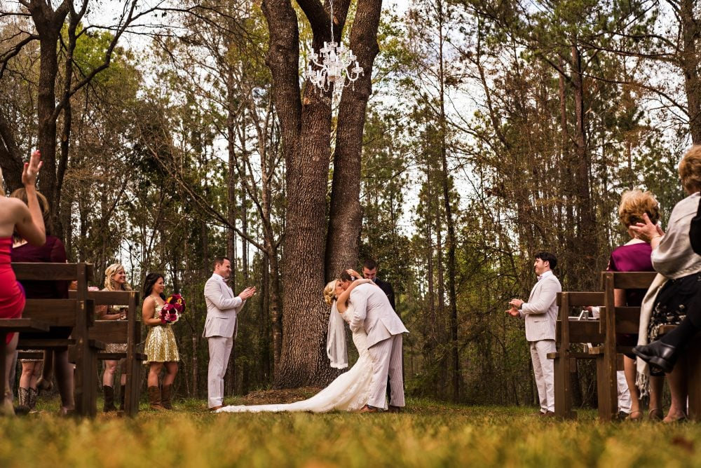 Real bride Lindsay and her groom during their wedding ceremony in a forest.