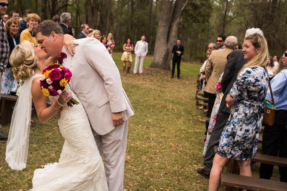 Bride and groom share a kiss amidst wedding guests in forest.