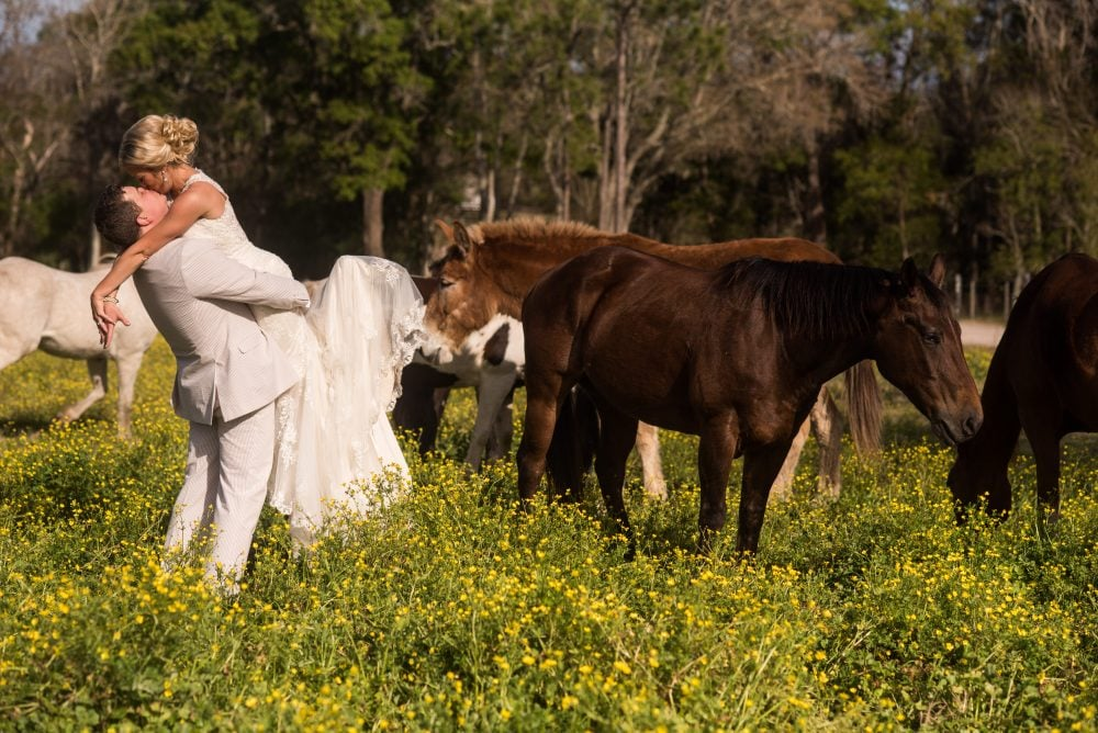 Bride and groom sharing a hug in a flower filled ranch field with horses.