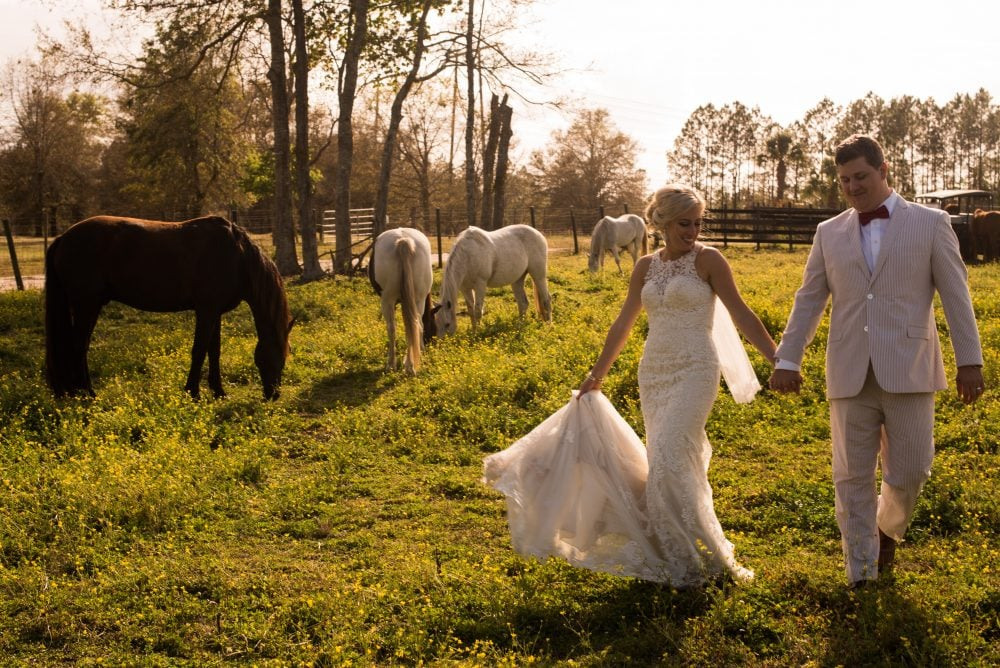 Bride and groom walking together and holding hands on wedding day in a ranch with horses.