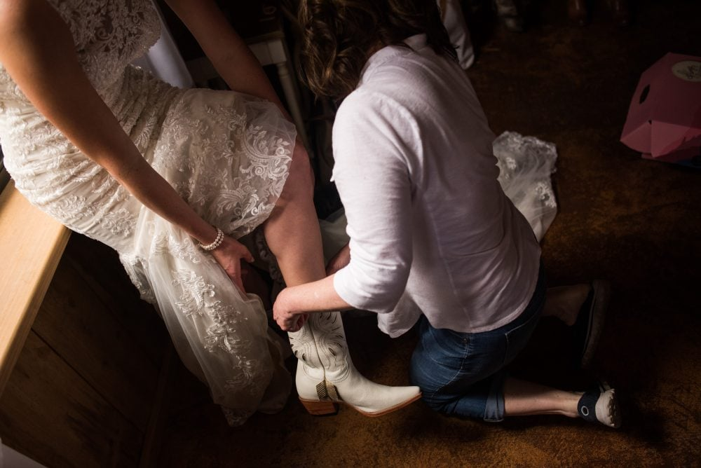 Real bride Lindsay putting on her cowboy boots for her barn wedding.