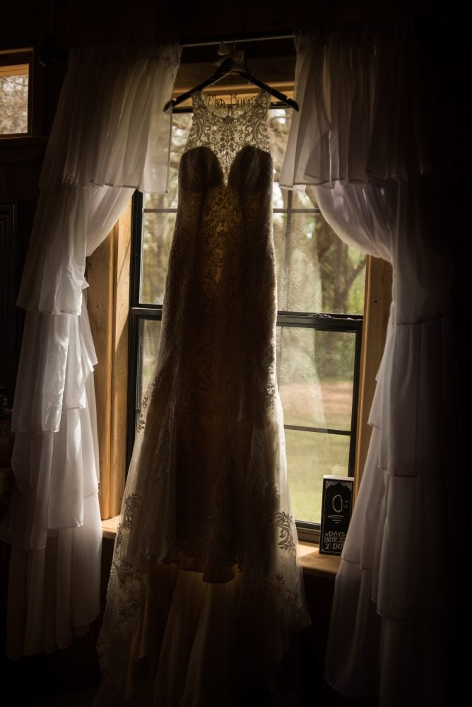 Hanging Essense of Australia wedding gown framed by the window.