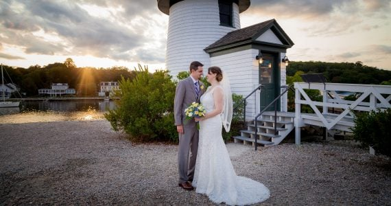 Real bride Megan with groom in front of lighthouse in Mystic, Connecticut.