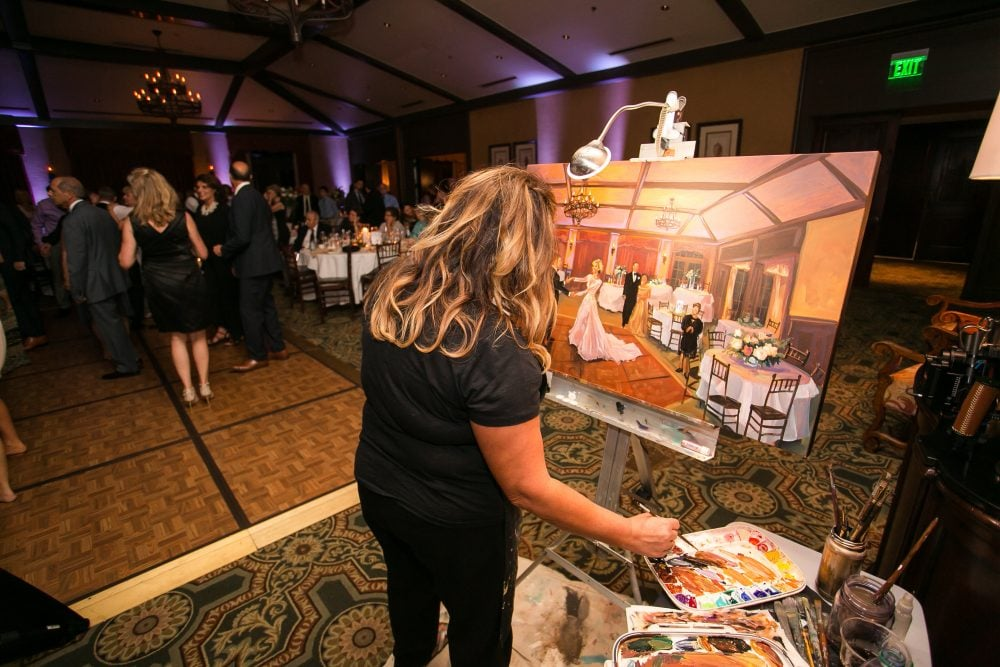 Wedding artist live painting the bride and groom's portrait during the reception.