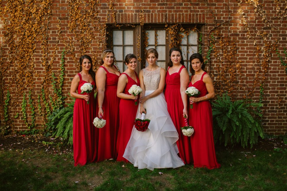 Real Bride Adrienne with her bridesmaids in red dresses on her wedding day in Ohio.