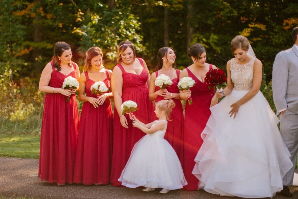 Real Bride Adrienne on her wedding day with her bridesmaids in red dresses and flower girl in white.