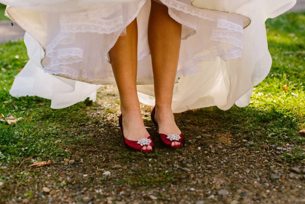 Real Bride Adrienne felt like Cinderella wearing her Hayley Paige dress paired with red heels on her wedding day.