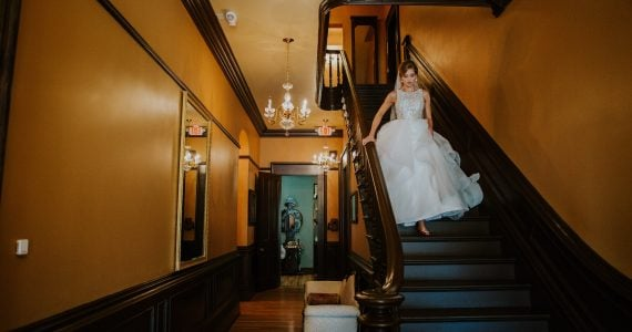 Real Bride Adrienne walking downstairs on her wedding day in Ohio.