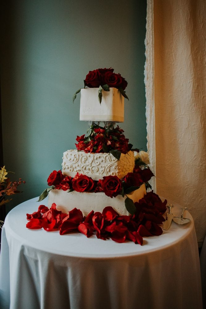 Real Bride Adrienne's three-tier wedding cake with red floral decorations from Sweet Grace Anna's in Ohio.