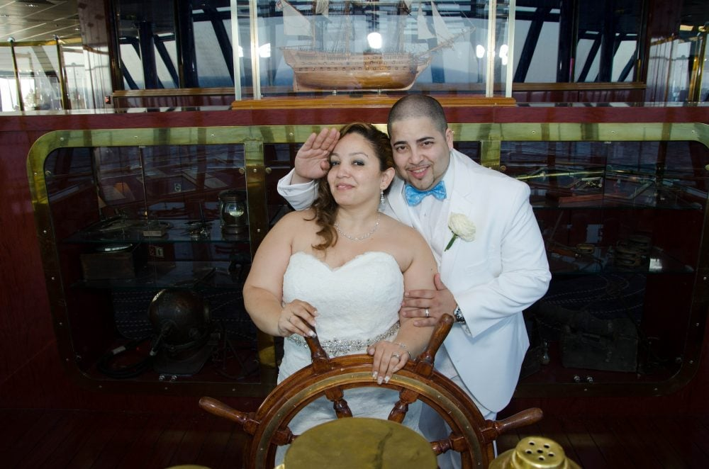 Real bride Zacha with groom, dressed in all white, on a cruise on their destination wedding day.