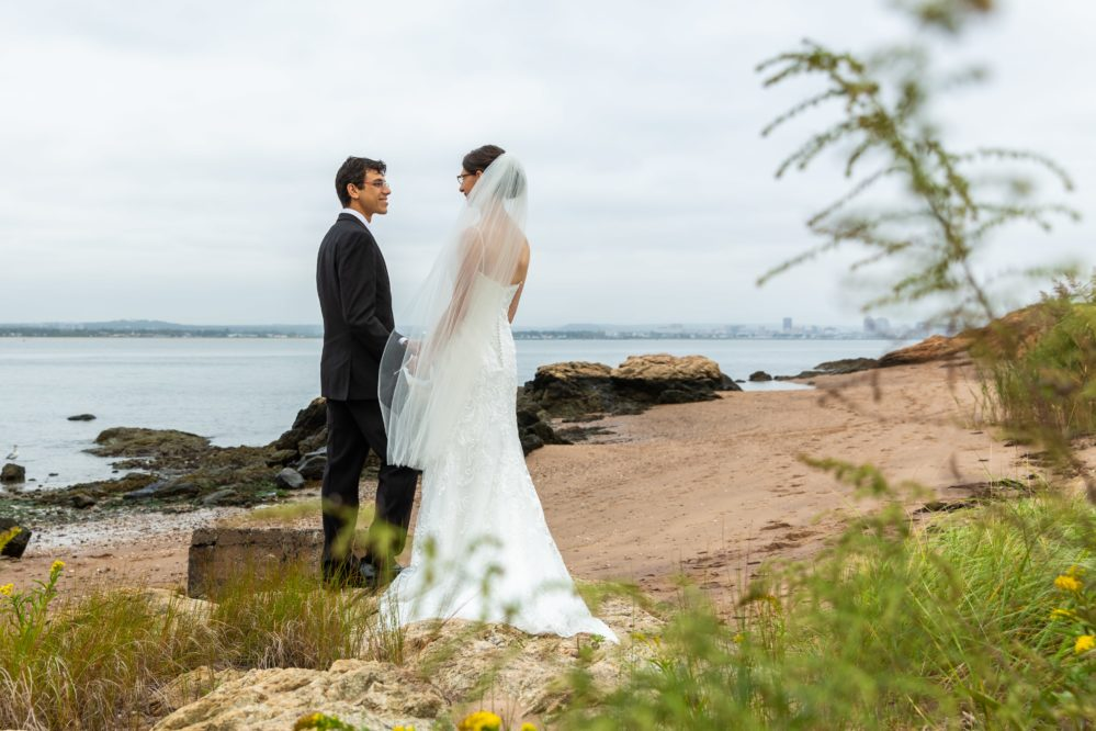 Real bride Shari and her groom sharing a wedding day moment on the beach in New Haven, CT.