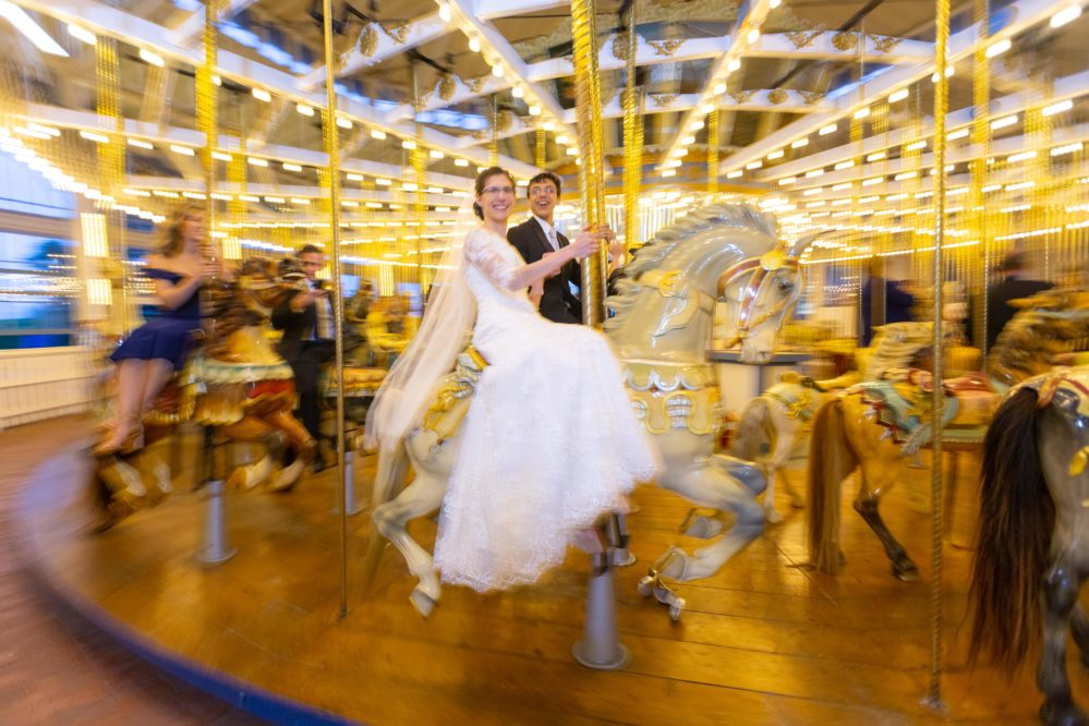 Bride and groom caught in action riding a merry-go-round on their wedding day.