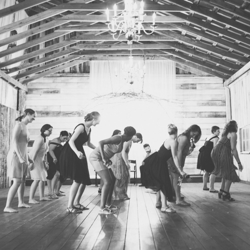 Black-and-white photo of Real bride Shelby's guests having a blast dancing on her wedding day in Columbia, TN.
