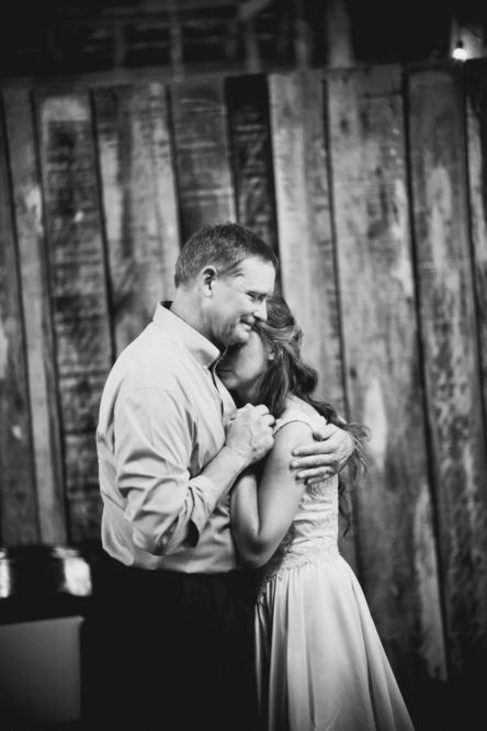 Black-and-white photo of Real bride Shelby dancing on her wedding day with her father.