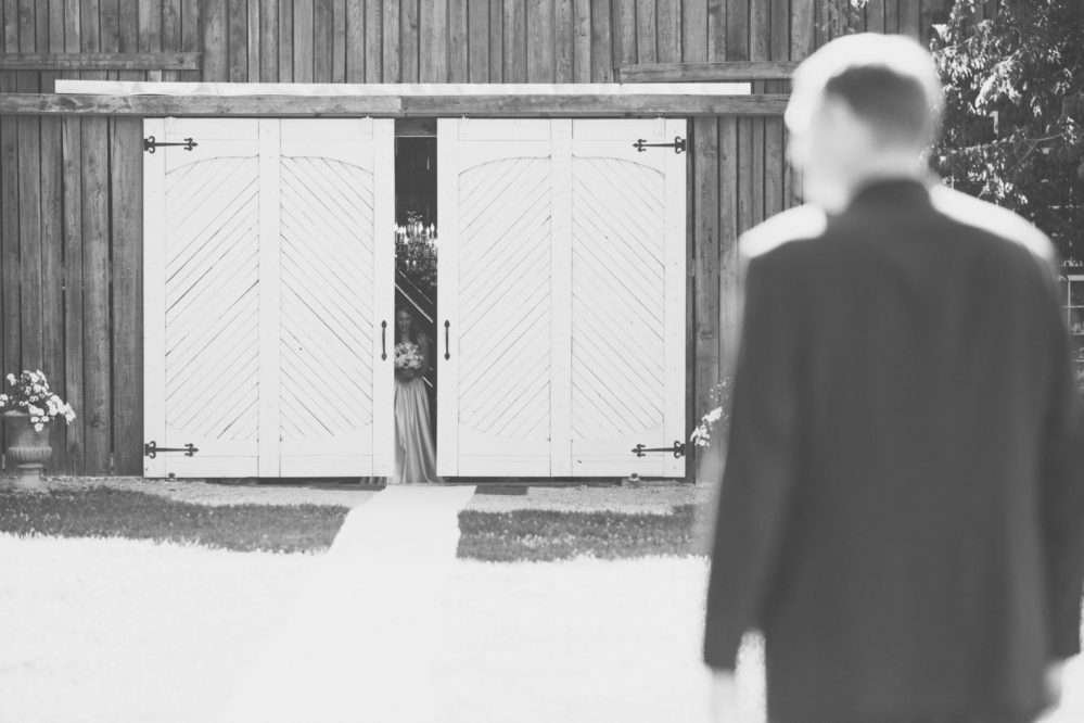 Real bride Shelby about to emerge from the barn setting of her Tennessee wedding.